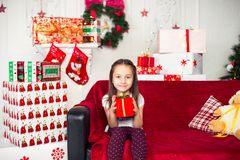 Little girl sitting on couch holding red box, gift Stock Image