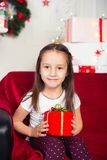 Little girl sitting on couch holding red box, gift Stock Photo