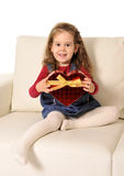 Little girl sitting on couch holding red heart shape cardboard cut Stock Image