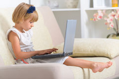 Little girl sitting on the couch with laptop Stock Photos