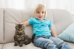 Little girl sitting on the couch stroking her cat Stock Photos