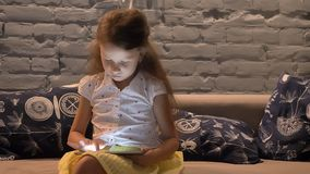Little girl sitting on couch and typing on tablet, kid playing on gadget, child at home concept, indoors stock video