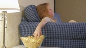 A little girl is sitting on the couch watching TV and eating popcorn. 4k stock footage