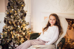 Little girl sitting on cozy wrapped in a blanket chair Christmas tree morning at home Royalty Free Stock Images