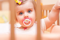 Little girl sitting in a crib with Stock Images