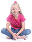 Little girl sitting cross-legged. Full body of a beautiful little Caucasian blond smiling preteen girl child in casual clothes sitting cross-legged on the floor Royalty Free Stock Photo