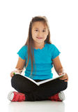 Little girl sitting cross legged and learning Stock Images