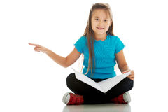 Little girl sitting cross legged and learning Royalty Free Stock Photo