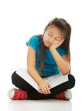 Little girl sitting cross legged and learning Stock Photo