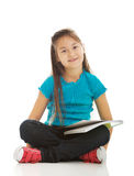 Little girl sitting cross legged and learning Royalty Free Stock Image