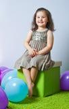 Little girl sitting on cube Stock Photo