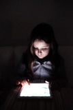 Little girl, sitting in a dark, playing with tablet Royalty Free Stock Images