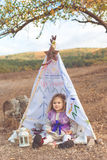 Little girl is sitting in decorative hovel Royalty Free Stock Photo