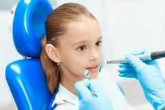 A little girl at a reception with a dentist. Female doctor preparing to examine the teeth of a girl. A little girl is sitting in a dental chair at a dentist`s stock images
