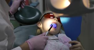 A little girl is sitting on a dental chair with an open mouth. Unrecognisable woman dentist treats teeth of little girl. UV lamp. Health and dental care. 4K stock video footage