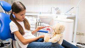 Little girl sitting in dentist chair and teachig her teddy bear how to properly clean teeth. Girl sitting in dentist chair and teachig her teddy bear how to royalty free stock photo
