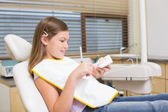 Little girl sitting in dentists chair looking at model teeth Stock Photos