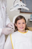 Little girl sitting in dentists chair smiling at camera Stock Photography