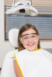 Little girl sitting in dentists chair wearing protective glasses Stock Photos