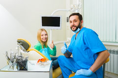 Little girl sitting in the dentists office and sjow thumbs up Royalty Free Stock Photo