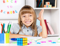 Little girl sitting at desk in the classroom Royalty Free Stock Images