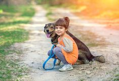 Little girl is sitting with a dog on the path royalty free stock photography