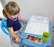 Little girl sitting drawing with watercolors in the children`s coloring. stock photography