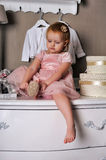 Little girl sitting on the dresser Stock Photography