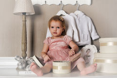 Little girl sitting on the dresser Stock Images