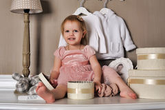 Little girl sitting on the dresser Royalty Free Stock Photo