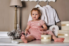 Little girl sitting on the dresser Royalty Free Stock Photography