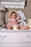 Little girl sitting on the dresser Stock Photo