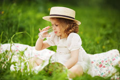Little girl sitting and drinking Royalty Free Stock Photos