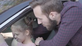 Little girl sitting on the driver`s seat of the car holding wheel close up. The child is learning to drive the car. Smiling bearded man standing at the car stock video