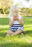 Little Girl Sitting and Eating Apple Outdoors Royalty Free Stock Photo