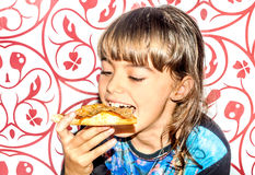 Little girl sitting and eating pizza slice Stock Photo