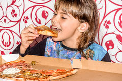 Little girl sitting and eating pizza slice Royalty Free Stock Image