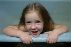 Little girl is sitting in an empty bathroom. royalty free stock image