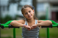 Little girl sitting on exercise equipment in the public park. Royalty Free Stock Photography