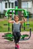 Little girl sitting on exercise equipment in the public park. Sport. Stock Photo