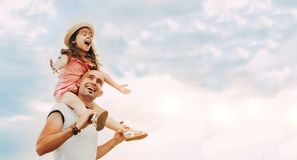 Little girl sitting on father`s shoulders stock photos