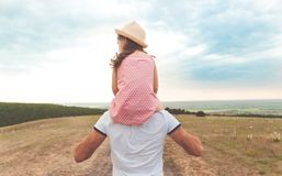 Little girl sitting on father`s shoulders Royalty Free Stock Images