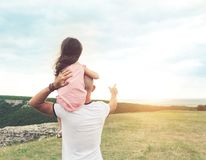 Little girl sitting on father`s shoulders Stock Images