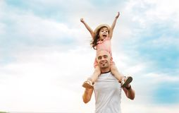 Little girl sitting on father`s shoulders stock image