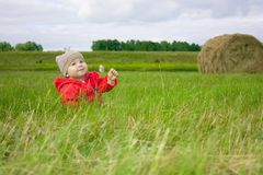 Little girl sitting in field Stock Images