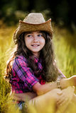 Little girl sitting in a field wearing a cowboy hat Royalty Free Stock Photo