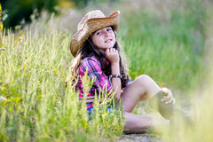 Little girl sitting in a field wearing a cowboy hat Royalty Free Stock Photography