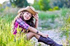 Little girl sitting in a field wearing a cowboy hat Stock Photo