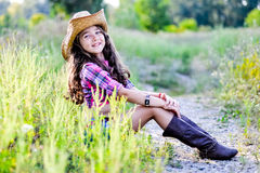 Little girl sitting in a field wearing a cowboy hat Stock Photography