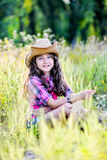 Little girl sitting in a field wearing a cowboy hat Stock Image